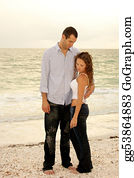 Tall-And-Short - Young Man Holding Woman In Front Of Ocean Looking Down At Her
