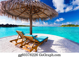 Two chairs and umbrella on tropical beach